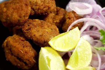 Mutton Tikki next to wedges of lime and slices of onion