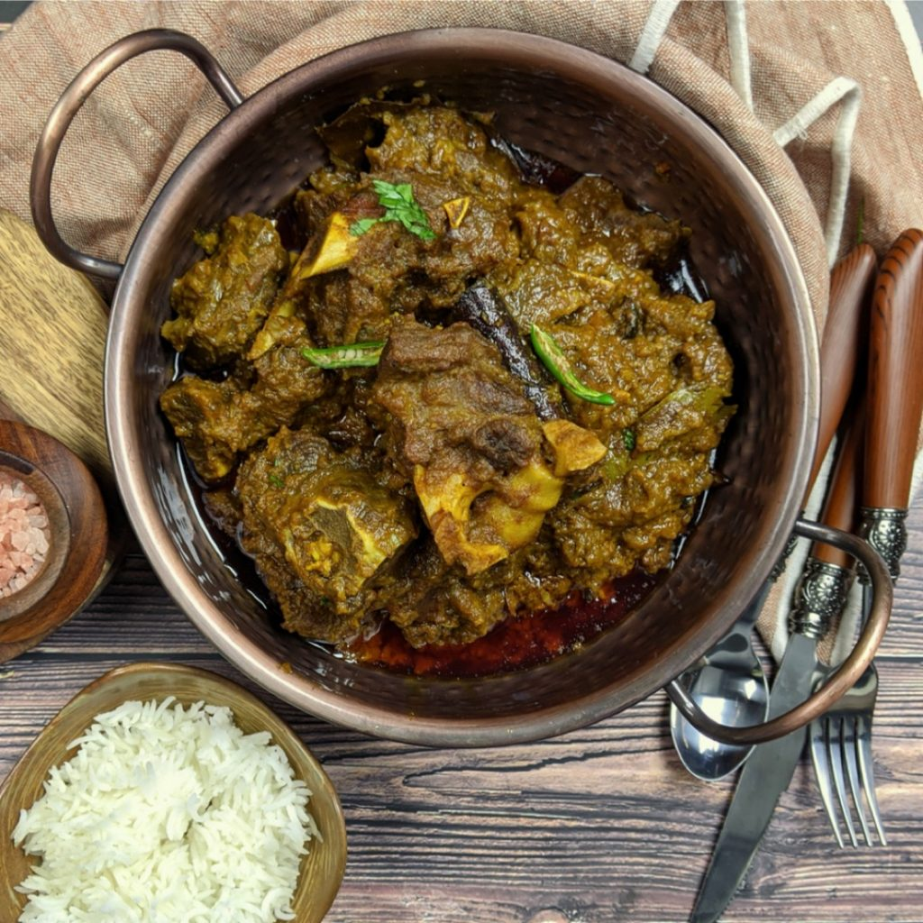Green Mutton Curry in a kadhai with rice and whole spices on the side.