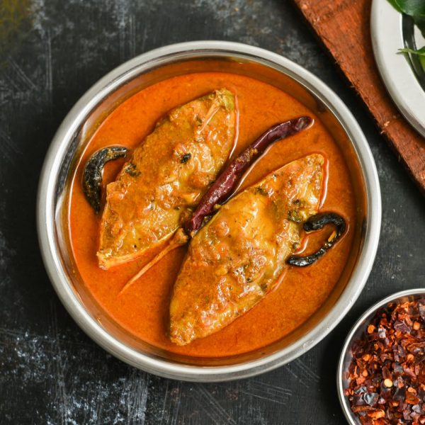 Pomfret Fish Curry in a silver bowl with curry leaves and red chillies.