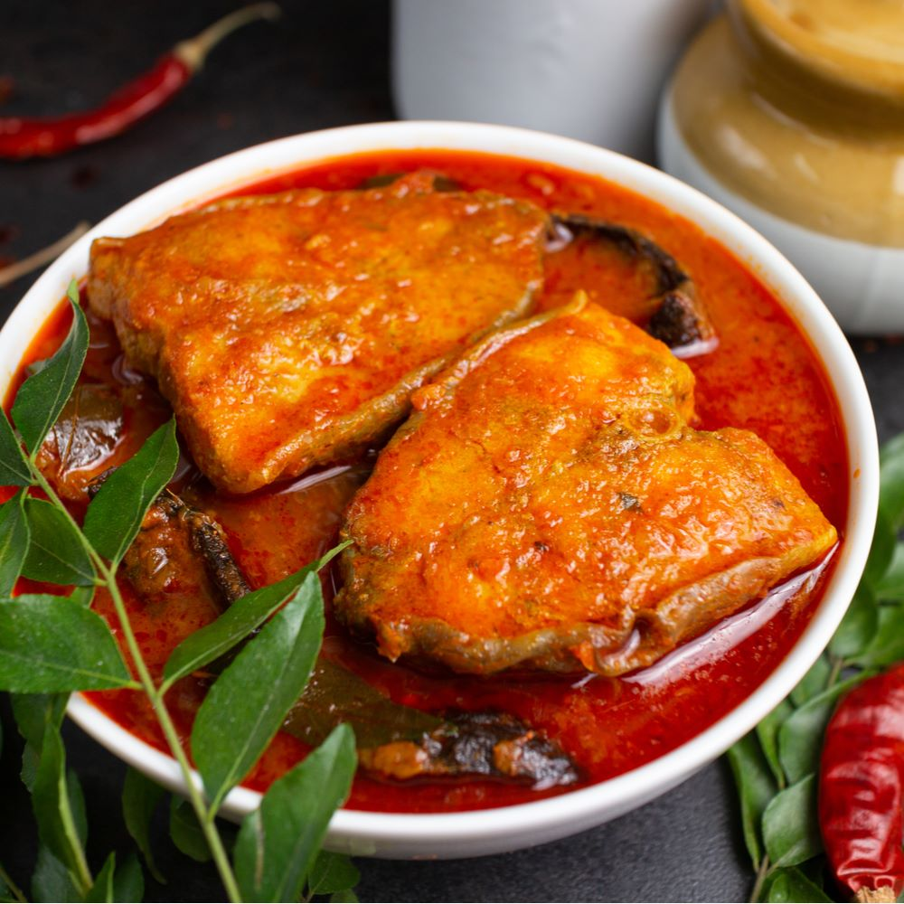 Basa Fish Curry in a white bowl with curry leaves and red chillies.