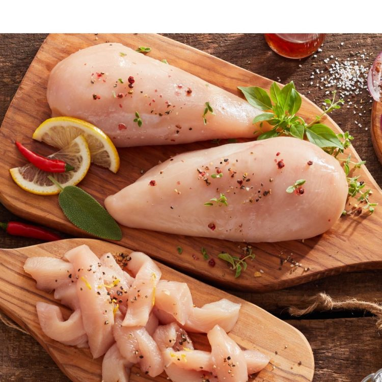 ifferent cuts of chicken placed on wooden boards.