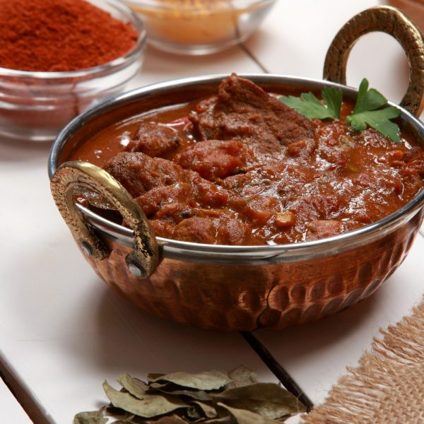 Kashmiri Mutton garnished with coriander leaves along with spices on the side.
