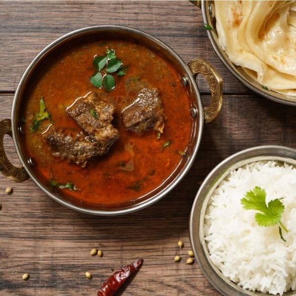 Mutton Ki Sabji with ghee rice and Malabar parathas on the side.