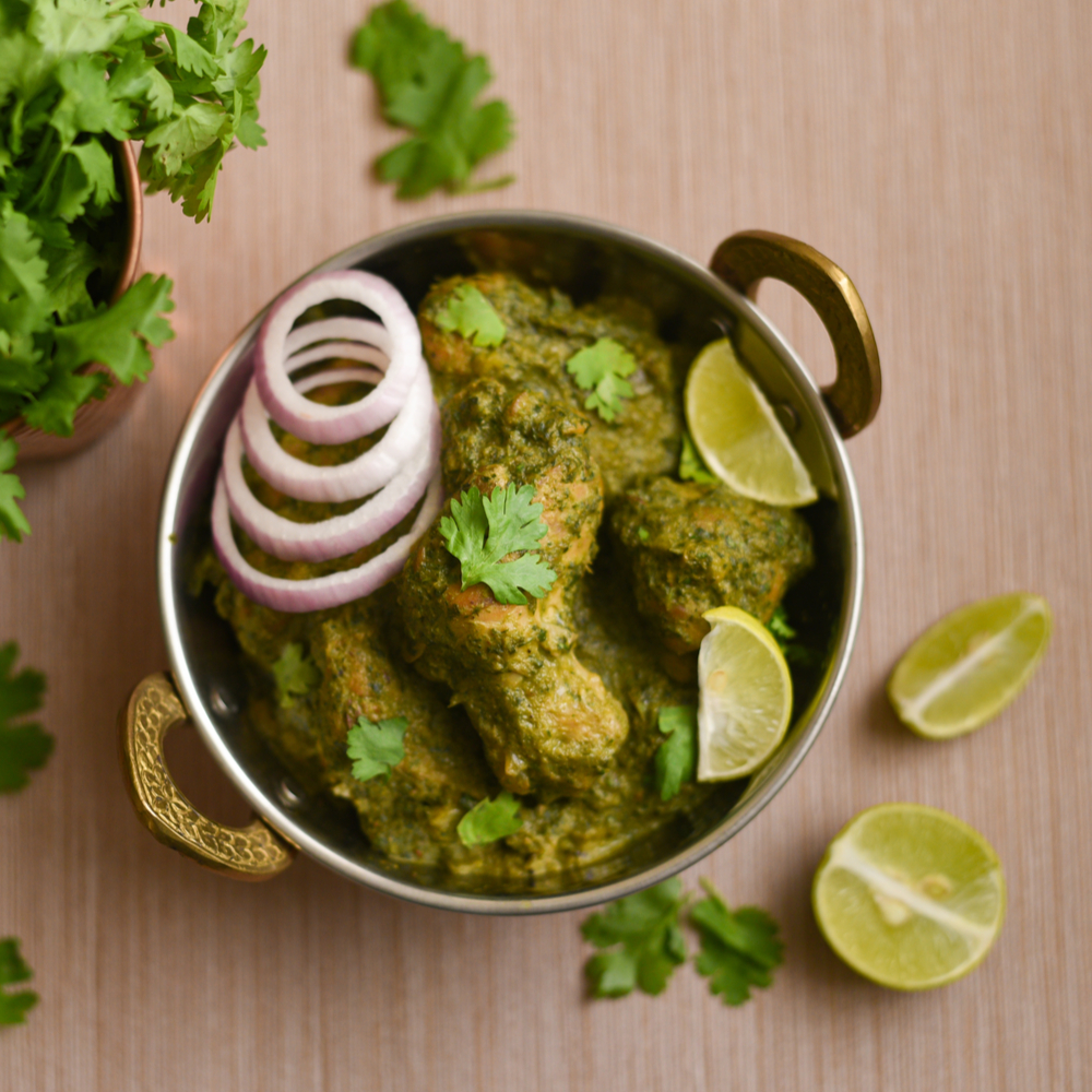Hariyali Chicken Curry in a brass bowl with onions, lime wedges and coriander beside it