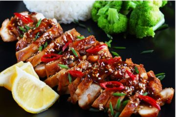 Teriyaki Chicken garnished with sesame seeds and chilly with lime on the side.
