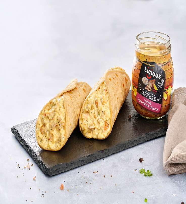 It's a picture of one of the Licious meat spread jars open on a platter. There are two wraps that are filled with the spread beside the jar. There is also a grey napkin on the right hand side.  The background of the image is also grey.