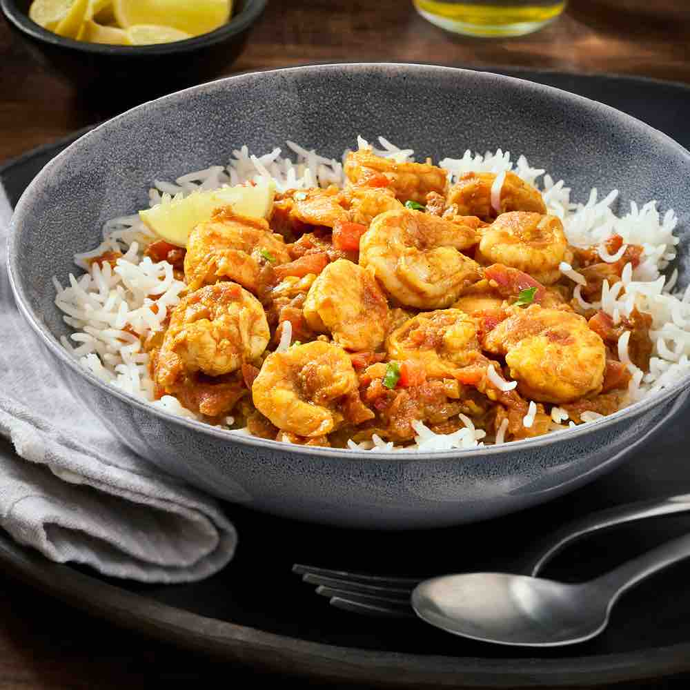 Prawns in a tomato gravy on a bed of rice, served in a grey bowl, with lemon wedges on side