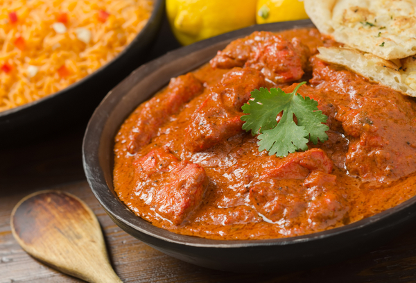 A delicious bowl of creamy chicken tikka masala with rice, lemons, and naan bread.